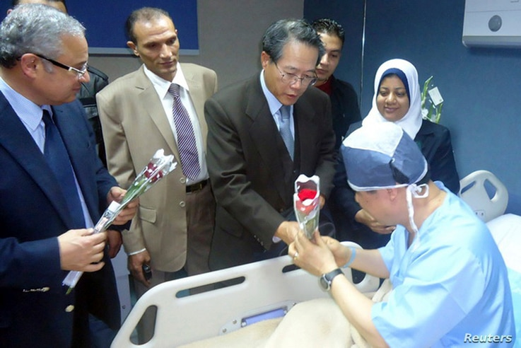 Egyptian Tourism Minister Hisham Zaazou (L) and South Korea's Consul to Egypt Lim Wan Shun (C) hand flowers to a South Korean tourist who was injured in a blast on a bus in Taba, at a hospital in Sharm El-Sheik hospital, southern Sinai, Feb. 17, 2014...