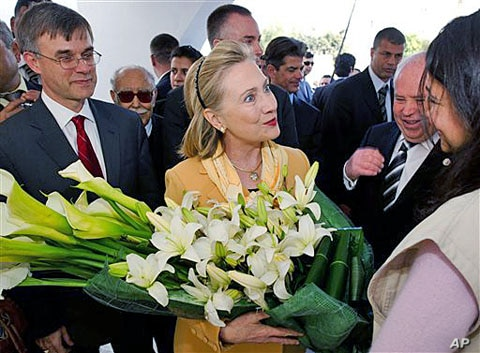 US Secretary of State Hillary Clinton is presented flowers as she tours the Red Crescent with US Ambassador to Tunisia Gordon Grey, left, in Tunis, March, 17, 2011