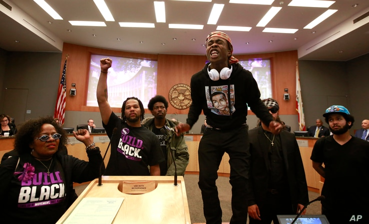 Stevante Clark stands on a desk as he shouts the name of his brother Stephon Clark, who was fatally shot by police a week earlier, during a meeting of the Sacramento City Council in Sacramento, California, March 27, 2018.
