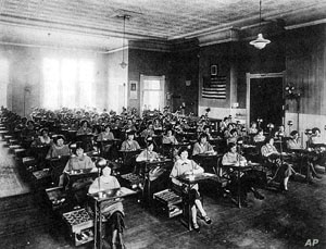 The women sit at their desks where they painted the watch faces, at the Radium Dial plant in Ottawa, Illinois, 1924.