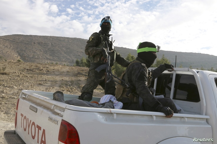 FILE - Fighters from the People's Protection Units (YPG), fighting alongside the Democratic Forces of Syria, ride on a pickup truck during what they said was an offensive against Islamic State militants to take control of Tishrin dam, south of Kobani