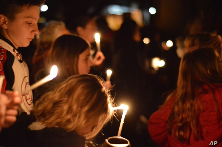 Aztec High School students and area residents gather for a candlelight vigil in Aztec, N.M., Thursday, Dec. 7, 2017, after a shooting at the high school.