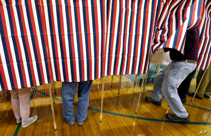 FILE - A voter enters a booth at a polling place in Exeter, N.H., Nov. 8, 2016. Donald Trump won the presidency, even as he lost the popular vote to Democrat Hillary Clinton. He nonetheless tweeted on Nov. 26 that he won the popular vote. and alleged...