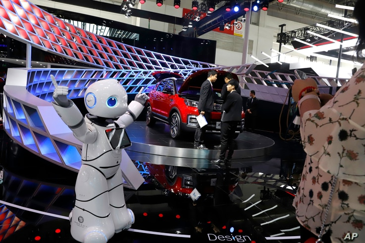 FILE - A robot entertains visitors at the booth of a Chinese automaker during the China Auto 2018 show in Beijing, China, April 26, 2018.