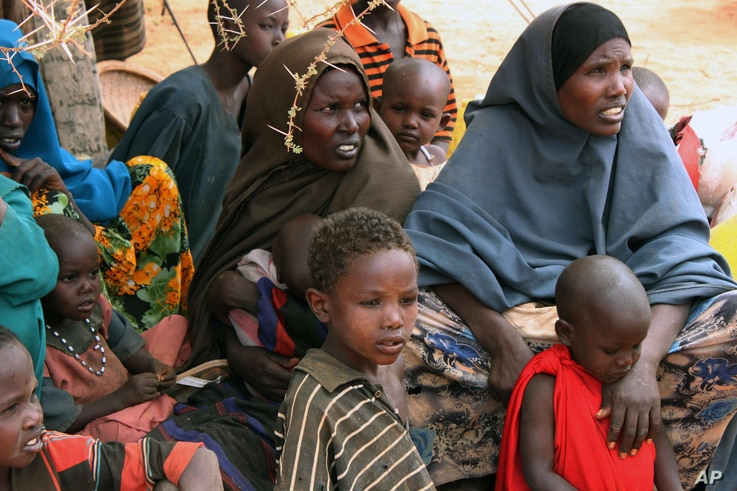 FILE - Somali women and children sit under a tree at a refugee camp in Dolo, Somalia while waiting for food rations.