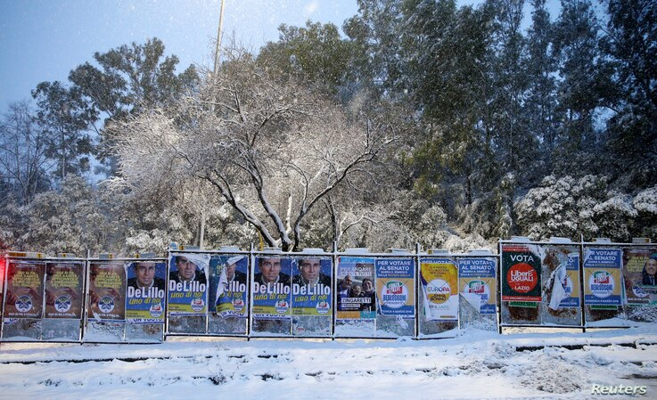 Electoral posters are seen during a heavy snowfall in Rome, Feb, 26, 2018.