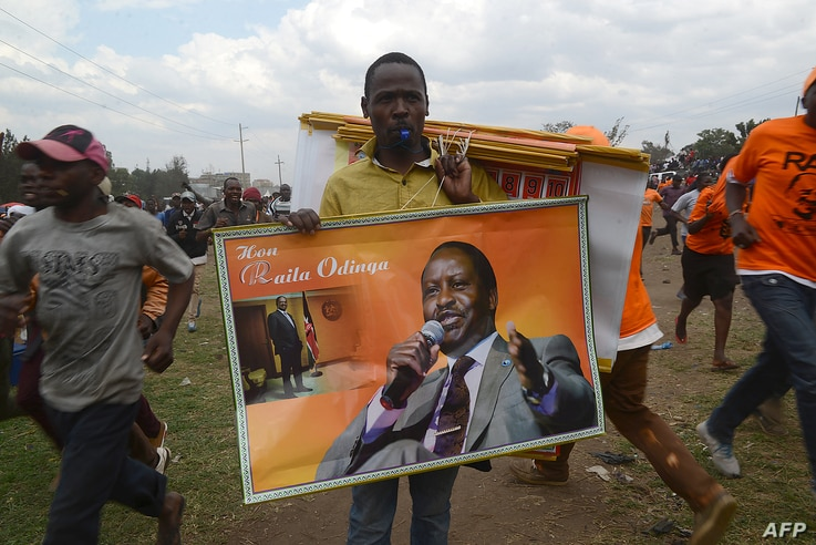 FILE - A vendor sells merchandise with images of Kenya's opposition leader Raila Odinga of the opposition National Super Alliance (NASA) coalition at a political rally Nairobi on Oct. 18, 2017.