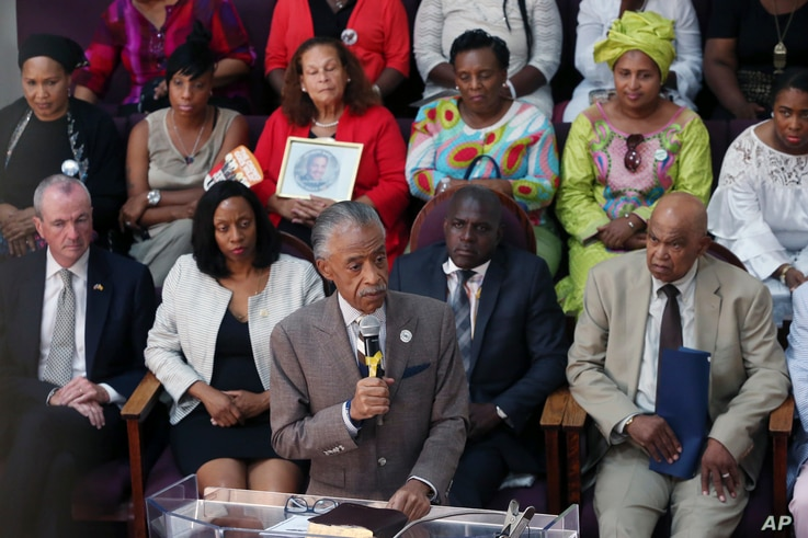 Rev. Al Sharpton, center at podium, speaks during services at Hope Memorial Baptist church, attended by many mothers of slain children, including Gwen Carr, mother of Eric Garner, Sunday, July 17, 2016, in Elizabeth, N.J.