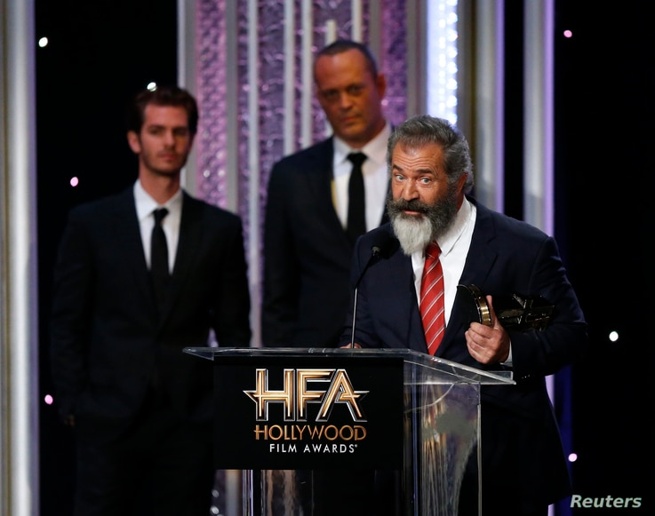"""Director Mel Gibson accepts the Hollywood Director Award for """"Hacksaw Ridge"""" as cast members Andrew Garfield, left, and Vince Vaughn look on at the Hollywood Film Awards in Beverly Hills, Calif., Nov. 6, 2016."""