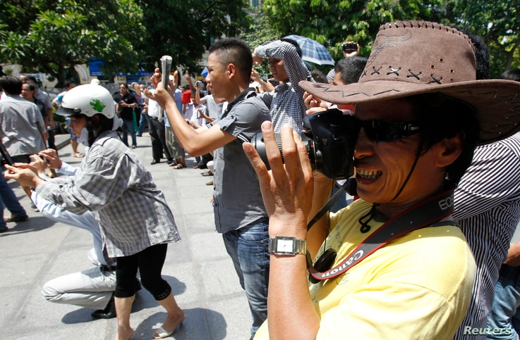 FILE - Blogger JB Nguyen Huu Vinh (front) takes photos while attending an anti-China protest in Hanoi.