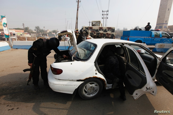 Police officers search a vehicle at a checkpoint,  as security increases after a bomb attack, at Abu Ghraib district, west of Baghdad, Iraq, Jan. 9, 2014.