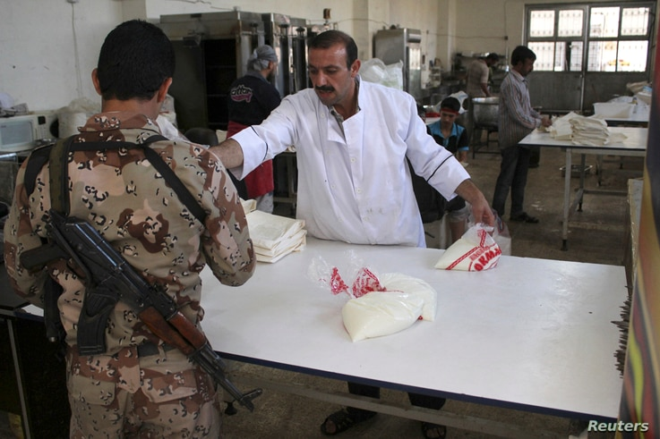 A Free Syrian Army cook hands his fellow fighter bags of yogurt in a kitchen located near the frontline in the al-Khalidiya neighborhood of Aleppo, Sept. 22, 2013.