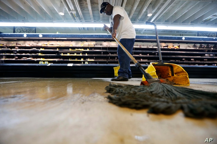 Randy Davis, manager at the Circle Food Store, mops the floor after the store flooded from the past weekend's torrential rains, in New Orleans, Aug. 7, 2017.