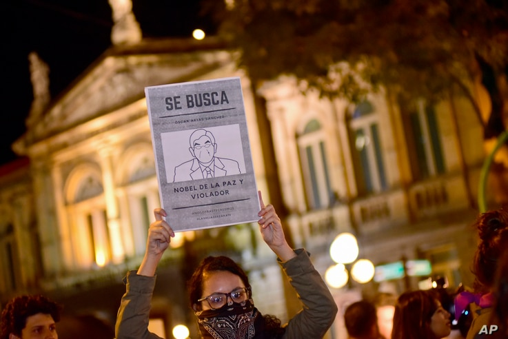 """FILE - A woman holds up a sign with a line drawing depicting Costa Rica's ex-President Oscar Arias and a message that reads in Spanish: """"WANTED: Oscar Arias Nobel Peace Prize laureate and Violator,"""" during a protest by women activists under the..."""
