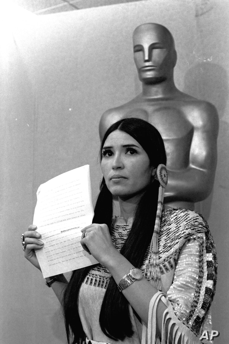 """FILE - Sacheen Littlefeather tells the audience at the Academy Awards ceremony that Marlon Brando was declining to accept his Oscar as best actor for his role in """"The Godfather,"""" March 27, 1973. The move was meant to protest Hollywood's treatment o..."""
