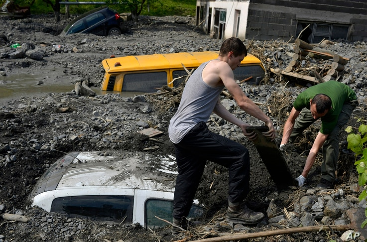 Residents try to excavate a car trapped in the mud caused by a landslide at the village of Topcic Polje, near Zenica, Bosnia-Herzegovina, May 20, 2014.