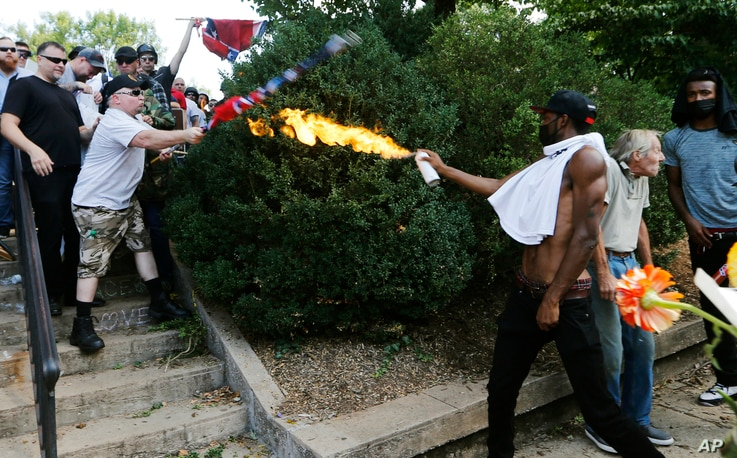 A counter demonstrator uses a lighted spray can against a white nationalist demonstrator at the entrance to Lee Park in Charlottesville, Va., Aug. 12, 2017.