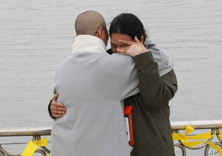 A relative of a passenger aboard the sunken ferry Sewol is consoled by a Buddhist nun, left, as she waits for news on her missing loved one at a port in Jindo, South Korea, Apr. 26, 2014.