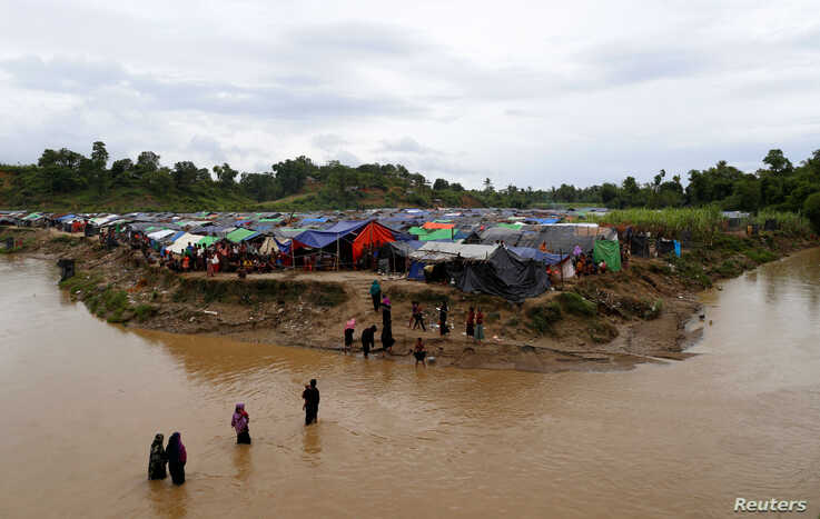 Rohingya refugees cross a stream to reach their temporary shelters at No Man's Land between the Bangladesh-Myanmar border, at Cox's Bazar, Bangladesh, Sept. 9, 2017.