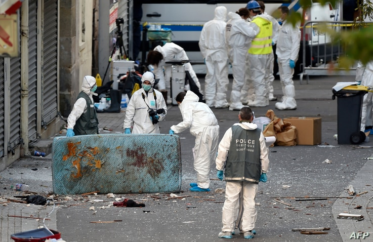 Forensics of the French police search for evidences outside a building in the northern Paris suburb of Saint-Denis, on November 18, 2015, where French Police special forces raided an appartment,