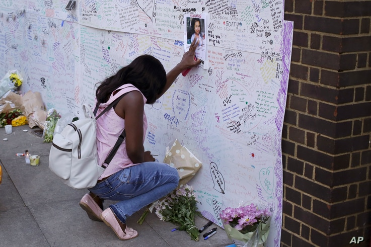 A woman touches a missing poster for 12-year-old Jessica Urbano on a tribute wall after laying flowers on the side of Latymer Community Church next to the fire-gutted Grenfell Tower in London, June 16, 2017.