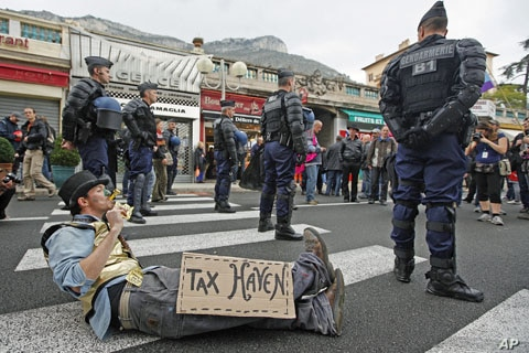 French gendarmes stand near an anti G20 demonstrator who takes part in protest against globalization and tax havens, at the French-Monaco border in Cap d'Ail, November 3, 2011.