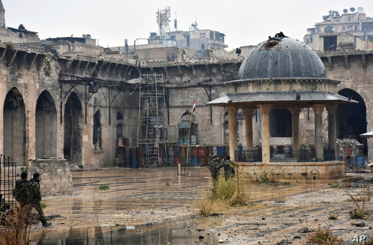 This photo released by the Syrian official news agency SANA shows Syrian troops and pro-government gunmen inside the destroyed Grand Umayyad mosque in the old city of Aleppo, Syria, Dec. 13, 2016. Government forces and rebel fighters have fought to c...