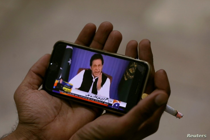 A journalist poses with a cell phone displaying Imran Khan, Prime Minister of Pakistan, speaking to the nation in his first televised address, in Karachi, Pakistan August 19, 2018.