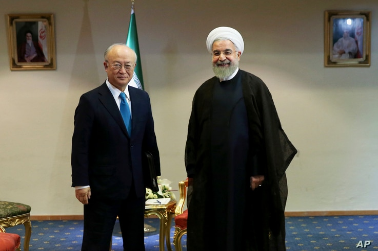 Iran's President Hassan Rouhani, right, welcomes the International Atomic Energy Agency's director-general, Yukiya Amano, as they pose for photos at the start of their meeting in Tehran, Iran, July 2, 2015.