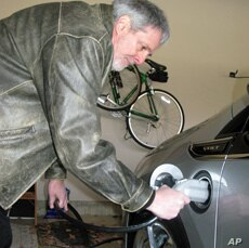 Volt owner Jeff Parmet disconnects the power cord from his new electric car.