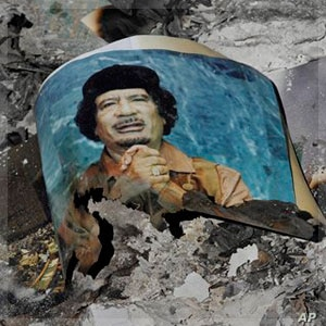 Picture of Libya's ousted leader Moammar Gadhafi is seen in the ashes in downtown Sirte, Libya, Wednesday, Oct. 12, 2011.  (AP Photo/Bela Szandelszky)