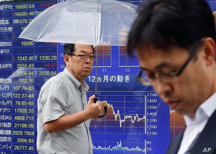 FILE - A man walks past an electronic stock indicator of a securities firm in Tokyo on June 7, 2016.