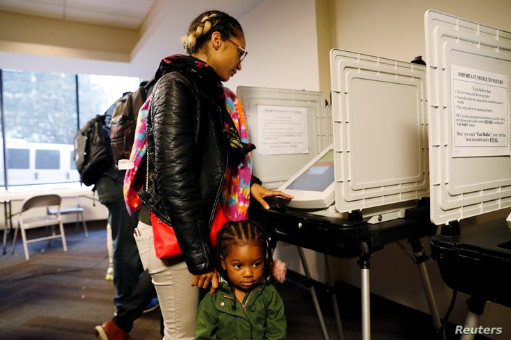 2-year-old Kadence Bethea waits for her mother Lindsey Adams to finish casting her vote in the U.S. midterm election after they waited in line for more than an hour and a half at a Fulton County polling place in Atlanta, Georgia, Nov. 6, 2018.