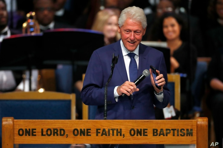 Former President Bill Clinton smiles as he plays a recording of Aretha Franklin on his phone during the funeral service for Franklin at Greater Grace Temple in Detroit, Aug. 31, 2018.