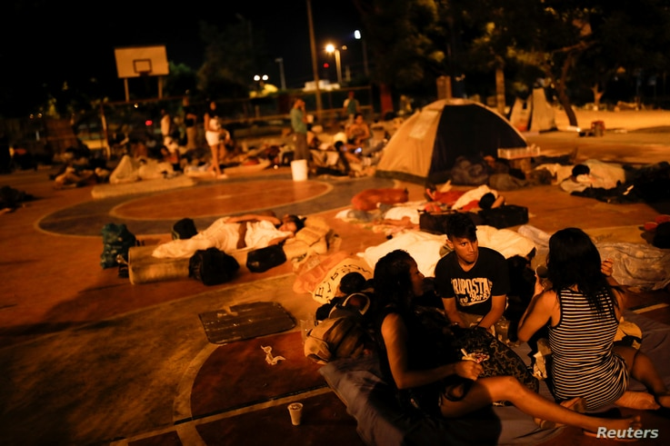 People prepare to sleep on the floor of a sports center, where a community of homeless Venezuelan migrants stays, in Cucuta, Colombia, Jan. 24, 2018.