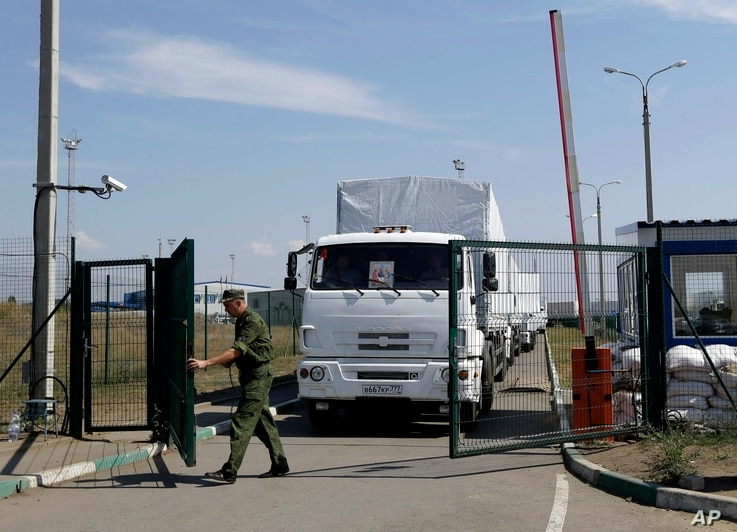 A Russian border guard opens a gate into the Ukraine for the first trucks heading into the country from the Russian town of Donetsk, Rostov-on-Don region, Russia, Friday, Aug. 22, 2014. The first trucks in a Russian aid convoy crossed into eastern Uk
