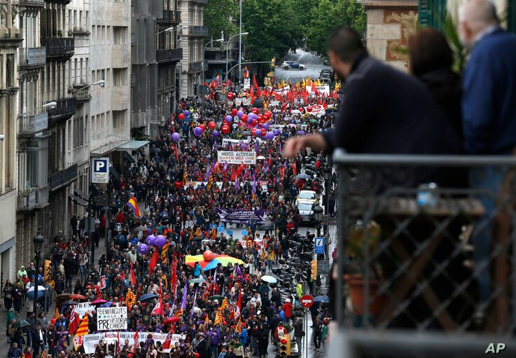 People march during a May Day rally in the center of Barcelona, Spain, Tuesday, May 1, 2018. May 1 is celebrated as the International Labor Day, or May Day, across the world.