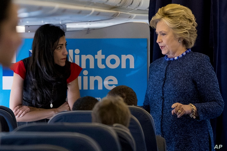 FILE - Democratic presidential candidate Hillary Clinton speaks with senior aide Huma Abedin aboard her campaign plane at Westchester County Airport in White Plains.