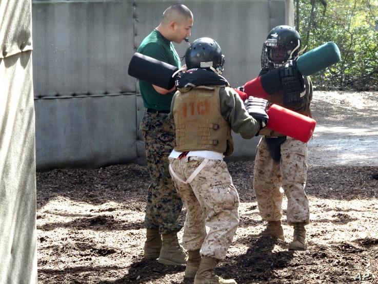 FILE - Female recruits battle with pugil sticks during training at the Marine Corps Training Depot on Parris Island, S.C., Feb. 21, 2013.