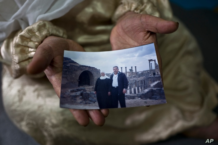 """FILE - Amineh Hamad, 58, a Syrian refugee from Eastern Ghouta, shows a photograph of herself and her husband Ali Abdulqader, 58, at her shelter in the Ritsona refugee camp, Greece, Jan. 7, 2017. """"It was the last time we visited the Roman site of Busr..."""