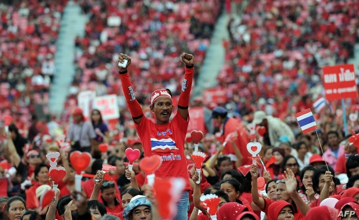 Thai pro-government Red Shirt supporters wave clappers and cheer leaders' speeches during a rally at a stadium in Bangkok, Nov. 30, 2013.