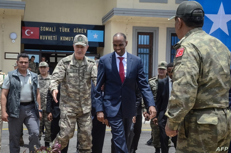 Turkish army Chief of General Staff Hulusi Akar, left, escorts Somalia Prime Minister Hassan Ali Kheire during an inauguration ceremony of the Turkish military base in Mogadishu on Sept. 30, 2017.