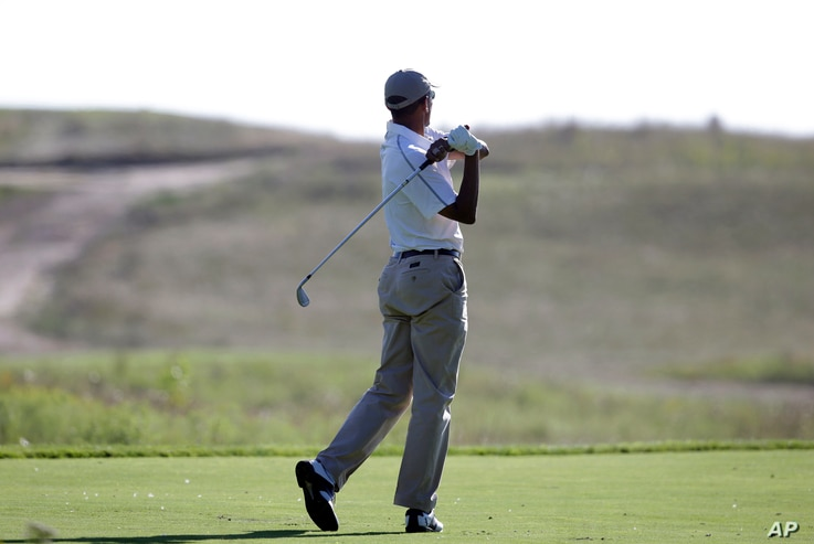 FILE - President Barack Obama follows through on a swing as he tees off while golfing at Vineyard Golf Club in Edgartown, Mass., Aug. 20, 2014. A day earlier, the U.S. government confirmed that American journalist James Foley had been beheaded by Isl...