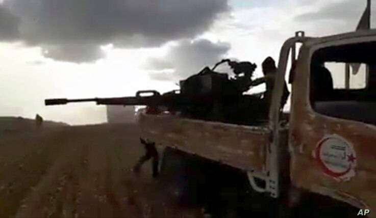This frame grab from video provided by Baladi News Network, a Syrian opposition media outlet, is said to show Turkey-backed Syrian opposition fighters fire their weapons during clashes near the northern Syrian town of al-Bab, Aleppo province, Syria, ...