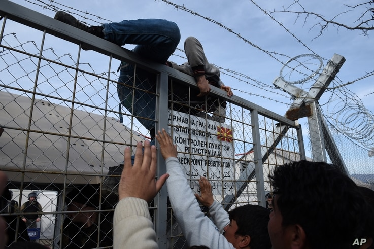 An Afghan refugee jumps the fence as he tries to enter Macedonia at the Greek-Macedonia borderline near the northern Greek village of Idomeni, Feb. 22, 2016.