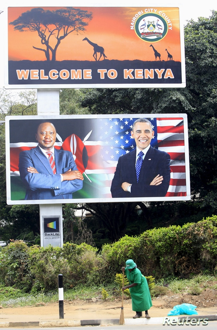 A woman sweeps next to a billboard displaying pictures of Kenya's President Uhuru Kenyatta (L) and visiting U.S. President Barack Obama, who is expected to arrive for a three-day state visit, in Kenya's capital Nairobi, July 24, 2015.