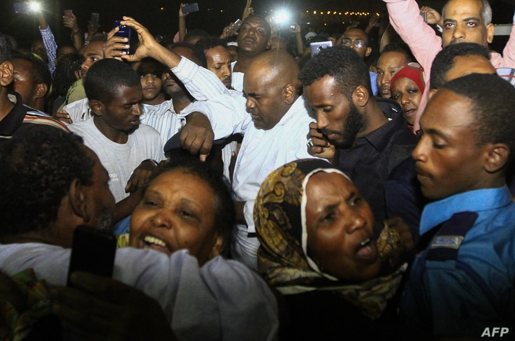 FILE - Family members welcome their loved ones after Sudan released dozens of opposition activists who were arrested last month when authorities cracked down on protests against rising food prices, outside the Kobar prison in north Khartoum on Feb. 1...