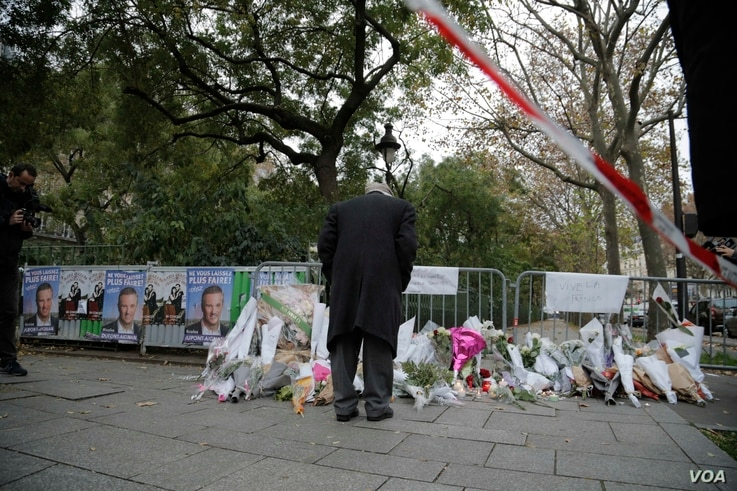 A man looks at the items left at a memorial outside the Bataclan Concert Hall a day after more than 120 people were killed in a series of attacks in Paris, Nov. 14, 2015.