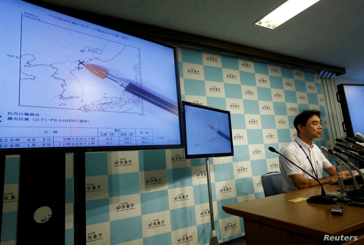 Japan Meteorological Agency's earthquake and tsunami observations division director Gen Aoki speaks next to screens showing the seismic event was indicated on North Korea and observed in Japan during a news conference at the Japan Meteorological Agen...