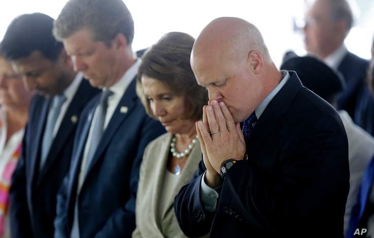From right, New Orleans Mayor Mitch Landrieu and House Minority Leader Nancy Pelosi listen to an invocation at a wreath-laying ceremony at the Hurricane Katrina Memorial on the 10th anniversary of Hurricane Katrina in New Orleans, Aug. 29, 2015.